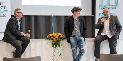 Kuopion Tieteen päivien puhujat nojailevat lukion juhlasalin lavaan.