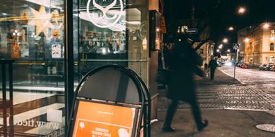 Kaupungin valot loistavat Helsingin Snellmaninkadulla. Valot heijastuvat Tiedekirja-kirjakaupan ikkunaan.