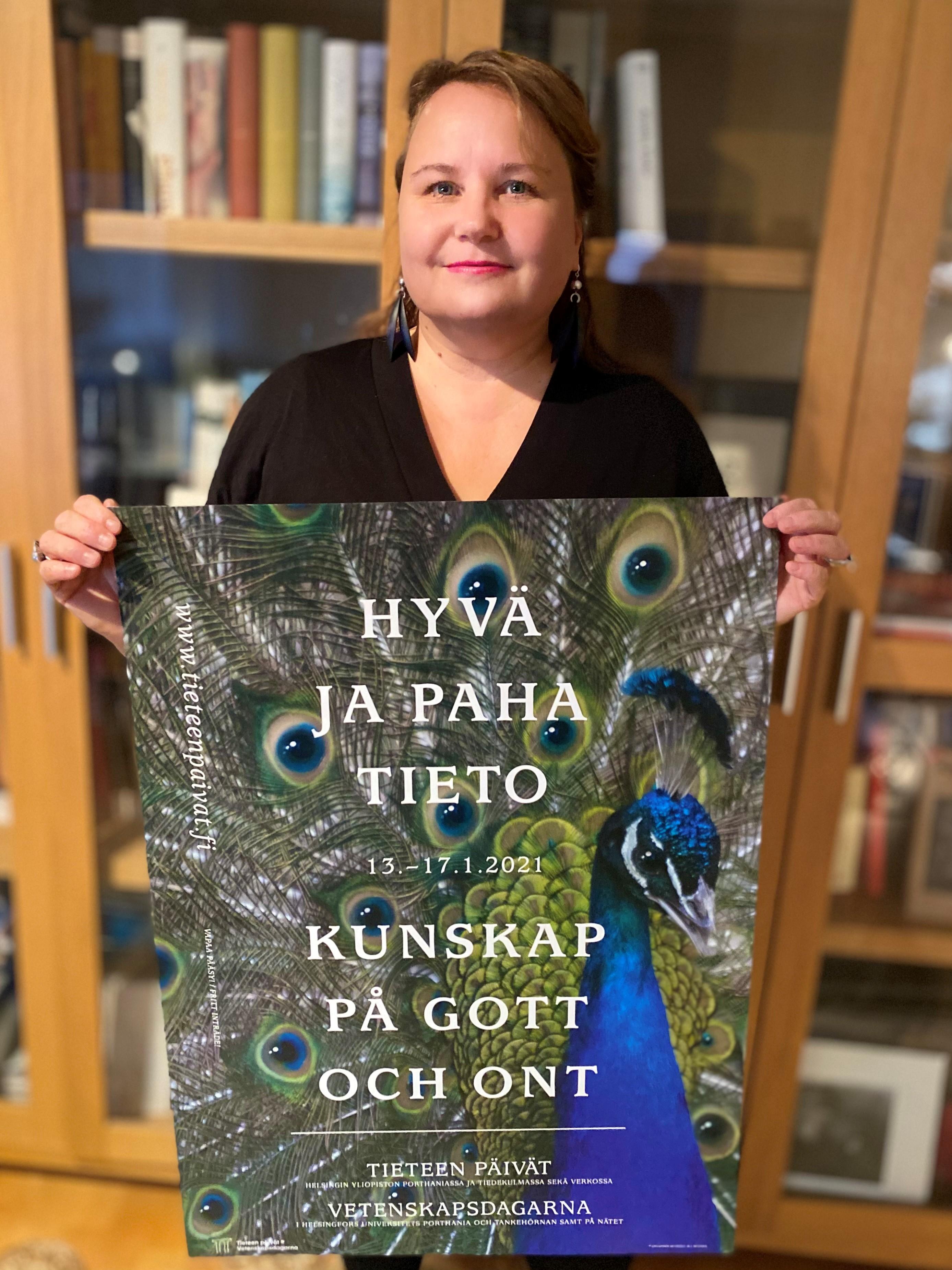 Graafinen muotoilija Marja-Leena Muukka pitelee Tieteen päivien 2021 julistetta käsissään.
