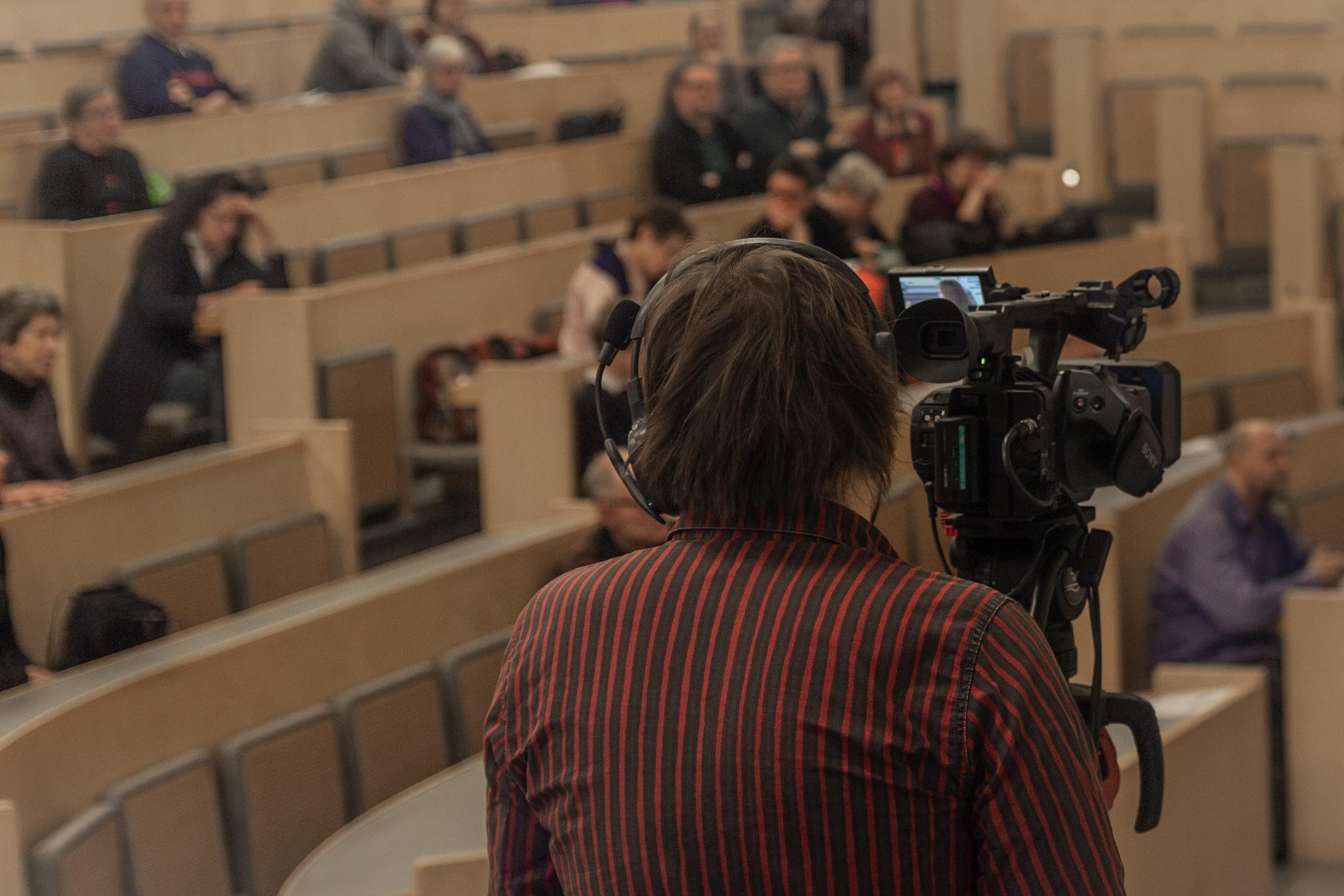 Nuori mies kuvaa Tieteen päivien ohjelmaa videokameralla.